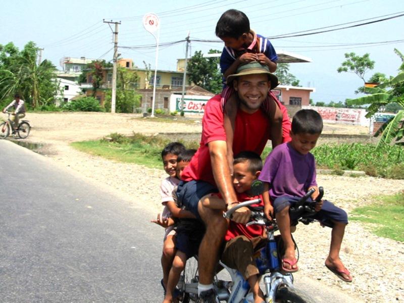 O brasileiro que viaja o mundo de bike para dar aula a crianças carentes