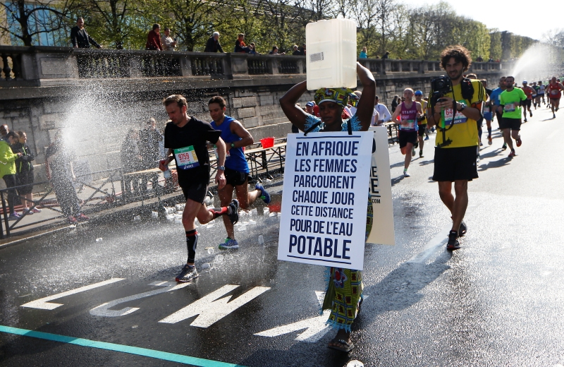 "Gambian woman Siabatou Sanneh displays a sandwich board which translates as ""In Africa women walk this distance each day for drinking water"" as she carries a jerrycan of water on her head while walking the route of the 39th Paris Marathon in Paris, on April 12, 2015, to raise awareness for the cause of charity ""Water for Africa"".    Siabatou Sanneh's symbolic participation in the 39th Paris Marathon while carrying a jerrycan of water on her head was to raise awarness of the plight of many people living in Africa who must walk great distances each day to obtain drinking water. AFP PHOTO / THOMAS SAMSON"