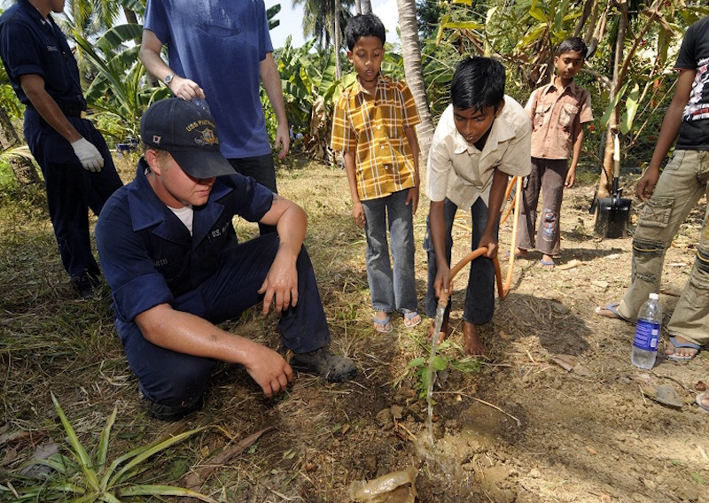 100324-N-8335D-148 PORT BLAIR, India (March 24, 2010) Mineman Seaman Derek Smith helps a boy from the Ramakrishna mission, an orphanage in Port Blair, plant a tree. Smith was one of 16 Sailors assigned to the mine countermeasures ship USS Patriot (MCM 7) who cleared ground to plant a garden of pomegranate, guava and lemon trees at the mission. Patriot is the first U.S. Navy warship to visit Port Blair and will be conducting military training with the Indian navy. (U.S. Navy photo by Mass Communication Specialist 1st Class Richard Doolin/Released)